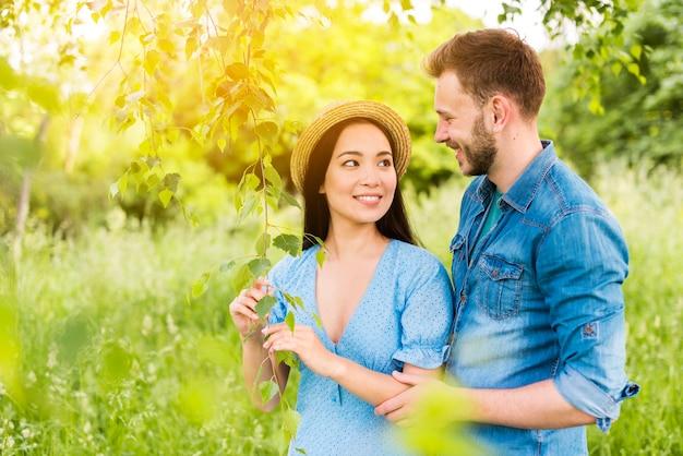 Giovani coppie allegre che sorridono a vicenda con amore in natura