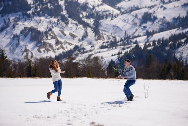 Giovani coppie amorose ad una data nella cima di una montagna innevata
