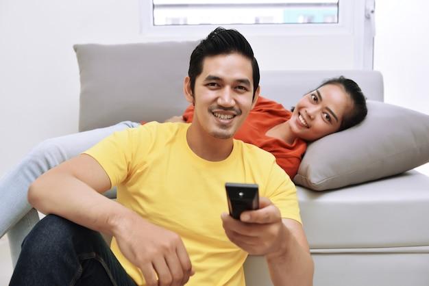 Giovani coppie amorose asiatiche che si rilassano e che guardano televisione
