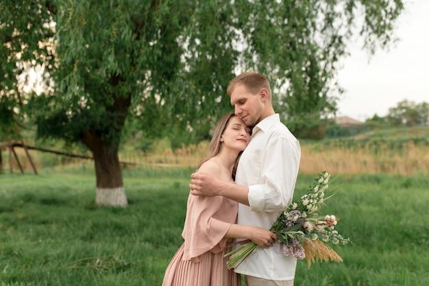 Giovani coppie amorose che abbracciano e che ballano sull'erba verde sul prato inglese. la donna e l'uomo belli e felici si toccano delicatamente. bella coppia innamorata. ragazza con il vestito e il ragazzo con la maglietta