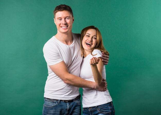 Giovani coppie amorose che guardano alla macchina fotografica contro fondo verde