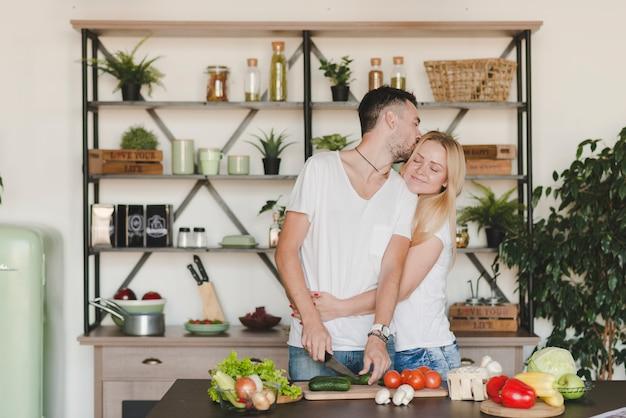 Giovani coppie amorose che preparano alimento nella cucina