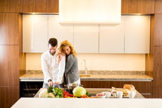 Giovani coppie amorose che preparano pasto gustoso in una cucina moderna