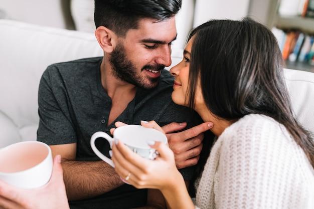 Giovani coppie amorose che se lo esaminano che tiene tazza di caffè