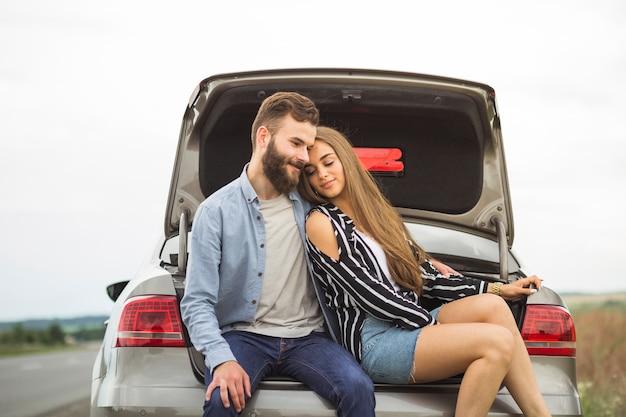 Giovani coppie amorose che si siedono nel tronco di automobile