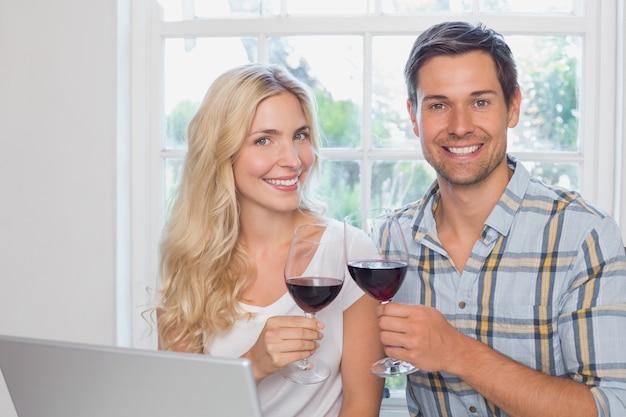 Giovani coppie amorose con bicchieri di vino a casa