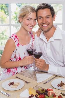 Giovani coppie amorose con bicchieri di vino al tavolo da pranzo