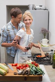 Giovani coppie amorose con i vetri di vino in cucina