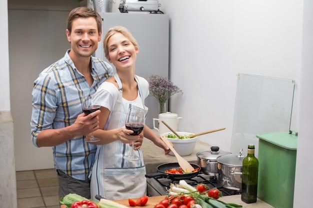 Giovani coppie amorose con il vetro di vino in cucina