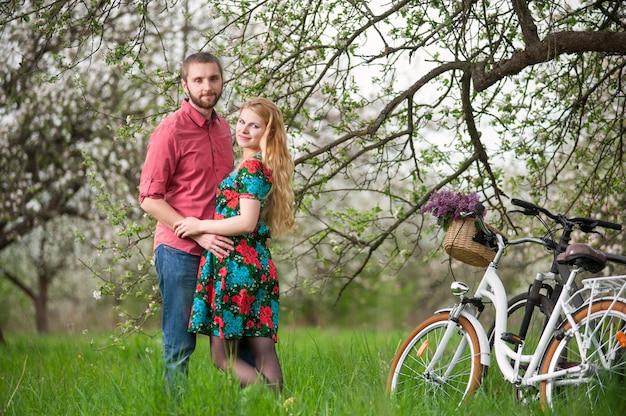 Giovani coppie amorose con le biciclette nel giardino di primavera