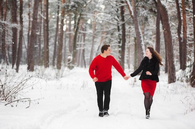 Giovani coppie amorose divertendosi con la neve nella foresta di inverno. ragazzo e ragazza godendo una passeggiata.