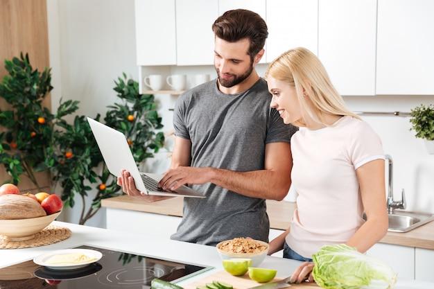 Giovani coppie amorose felici che stanno alla cucina e alla cottura