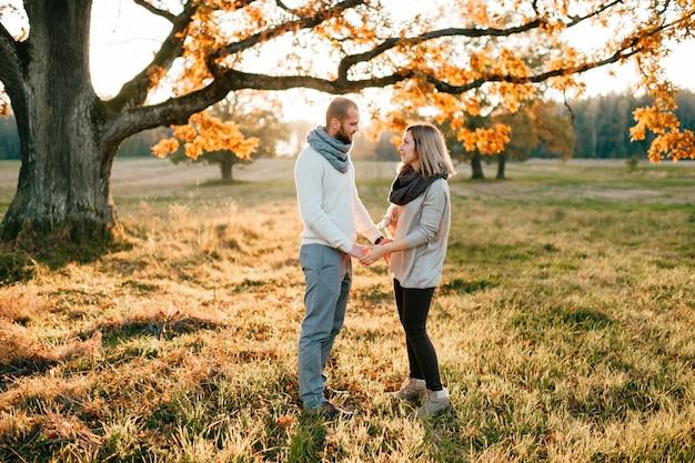 Giovani coppie amorose nel campo di autunno al tramonto