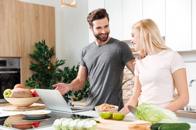 Giovani coppie amorose sorridenti che cucinano insieme facendo uso del computer portatile