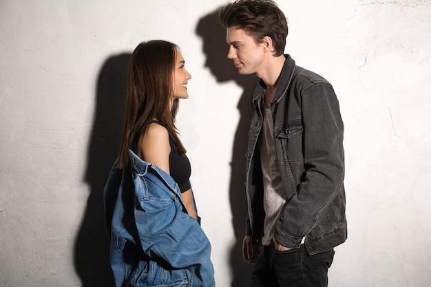 Giovani coppie amorose sorridenti che guardano da parte