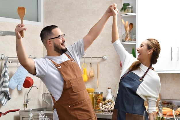 Giovani coppie asiatiche amorose che cucinano nella cucina che fanno insieme divertimento sano dell'alimento