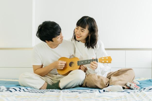 Giovani coppie asiatiche che giocano ukulele e che cantano insieme una canzone nella camera da letto