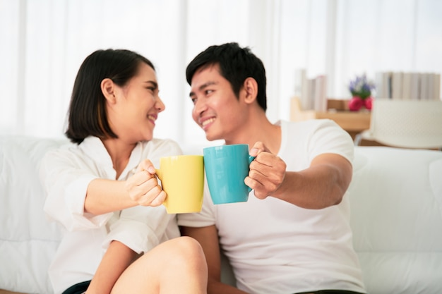 Giovani coppie asiatiche che godono insieme al caffè di mattina in badroom, svago, coppia, relazione e biglietto di s. valentino. fotografia con copyspace.