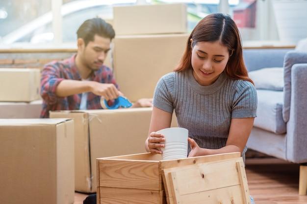 Giovani coppie asiatiche che imballano la grande scatola di cartone per muoversi