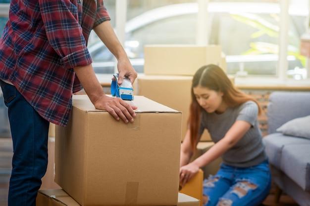 Giovani coppie asiatiche del primo piano che imballano la grande scatola di cartone per muoversi nella nuova casa