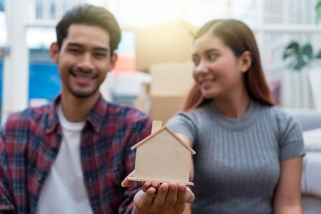 Giovani coppie asiatiche del primo piano che tengono il modello della casa