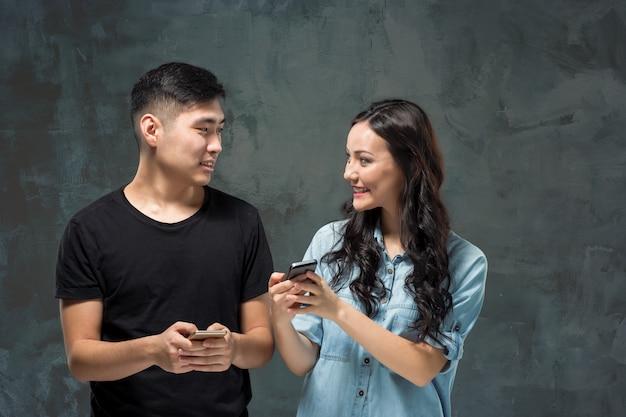 Giovani coppie asiatiche facendo uso del cellulare, ritratto del primo piano.