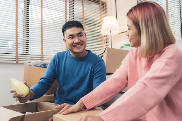 Giovani coppie asiatiche felici che si muovono verso la loro nuova casa, scatole aperte per controllare i vecchi oggetti da vecchia casa