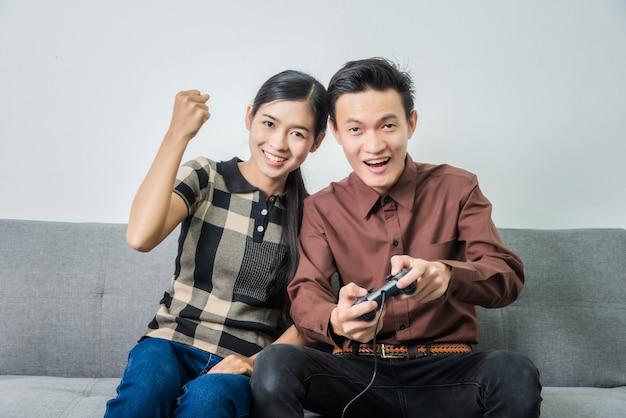 Giovani coppie asiatiche nell'amore e nei videogiochi che tengono leva di comando mentre sedendosi sul sofà in salone.