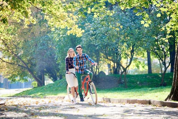 Giovani coppie attive attive del viaggiatore, uomo barbuto bello e donna bionda attraente che ciclano insieme la bici doppia in tandem lungo il percorso scoppiettante in illuminato dal sole luminoso di mattina bello parco sotto gli alberi.