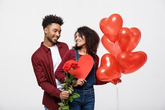 Giovani coppie attraenti dell'afroamericano sulla datazione con la rosa rossa, il cuore e l'aerostato.