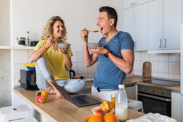 Giovani coppie attraenti dell'uomo e della donna che mangiano colazione insieme mattina alla cucina