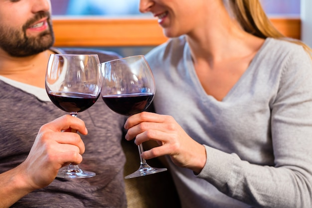 Giovani coppie belle che bevono vino rosso a casa