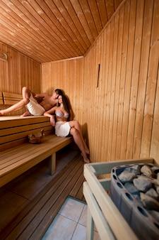 Giovani coppie belle che si rilassano nella sauna