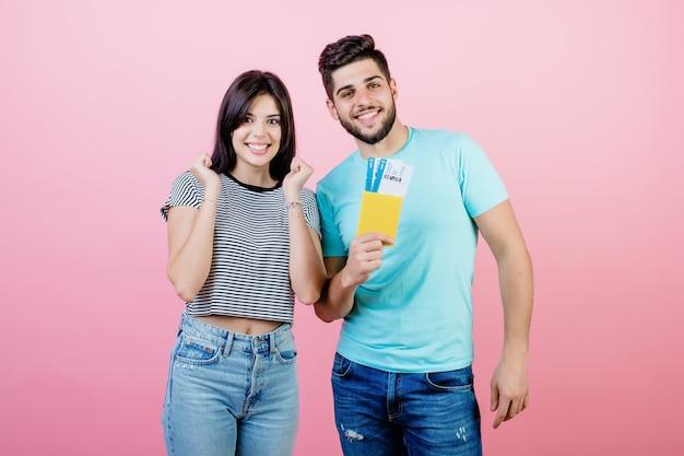 Giovani coppie belle uomo e donna con il passaporto e i biglietti aerei