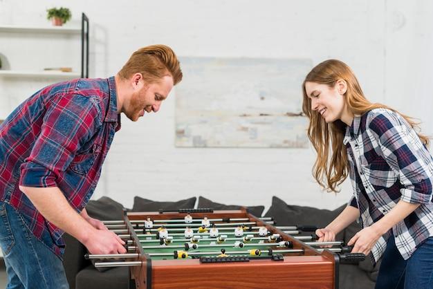 Giovani coppie bionde sorridenti che godono del gioco nel calcio-balilla