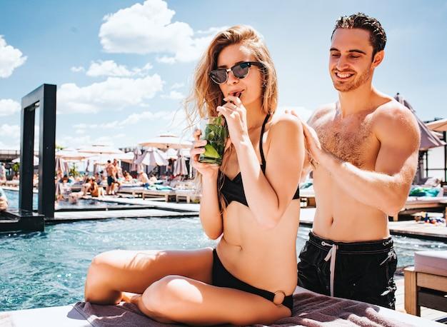 Giovani coppie calde che riposano allo swimpool.