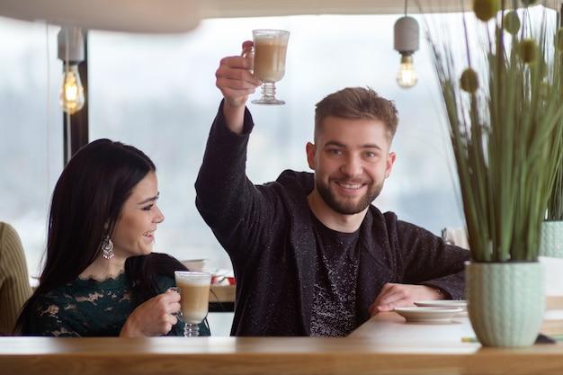 Giovani coppie caucasiche che parlano e che bevono caffè in caffè, saluti dell'uomo con la tazza di caffè a disposizione e che sorridono, ragazza che ride a quel tempo
