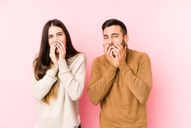 Giovani coppie caucasiche che ridono di qualcosa, coprendo la bocca di mani.