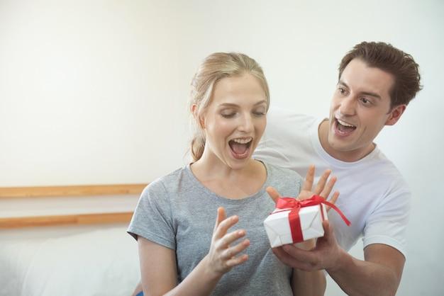 Giovani coppie caucasiche felici che celebrano a casa. l'uomo bello del ragazzo dà la sua ragazza con il contenitore di regalo sorprendentemente.