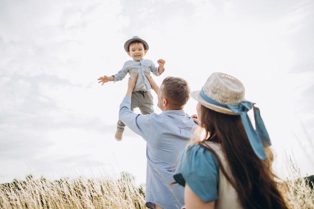 Giovani coppie caucasiche felici con il neonato. genitori e figlio si divertono insieme.