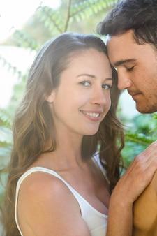 Giovani coppie che abbracciano appassionatamente in giardino