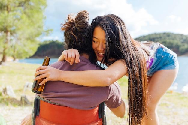 Giovani coppie che abbracciano mentre riposa sulla spiaggia