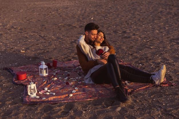 Giovani coppie che abbracciano sul copriletto sulla riva del mare