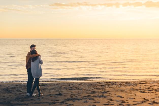 Giovani coppie che abbracciano sulla riva del mare in serata