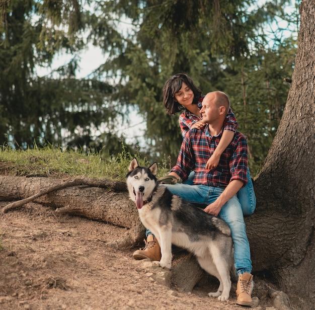 Giovani coppie che abbracciano vicino agli alberi delle montagne