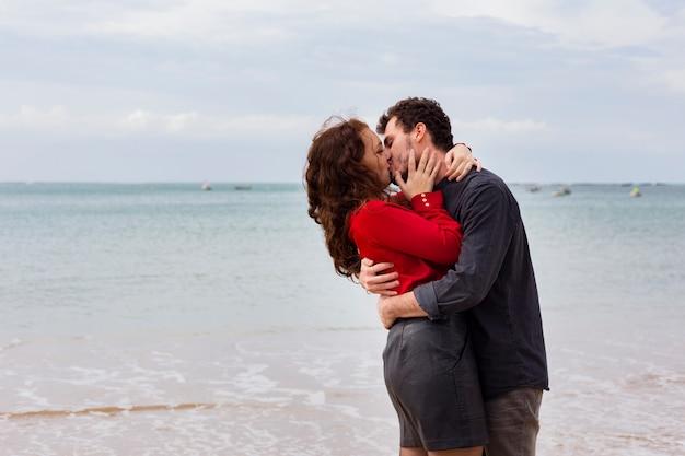 Giovani coppie che baciano sulla riva del mare sabbioso