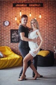 Giovani coppie che ballano musica latina: bachata, merengue, salsa. posa di due eleganza sul caffè con pareti in mattoni
