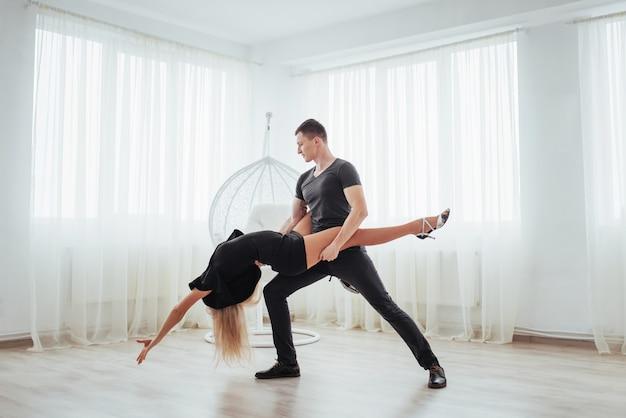 Giovani coppie che ballano musica latina: bachata, merengue, salsa. posa di due eleganza sulla stanza bianca