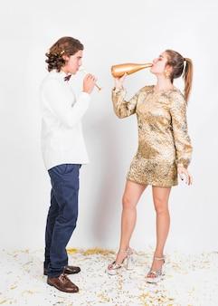 Giovani coppie che bevono champagne da vetro e bottiglia
