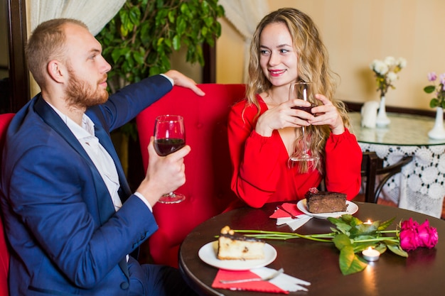 Giovani coppie che bevono vino al tavolo nel ristorante